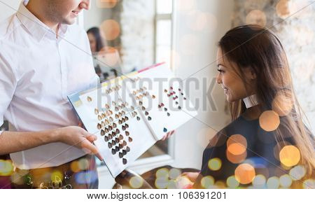 beauty, hair dyeing and people concept - happy young woman with hairdresser choosing hair color from palette samples at salon over holidays lights