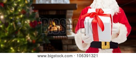 christmas, holidays and people concept - close up of santa claus with gift box over living room with fireplace and christmas tree background