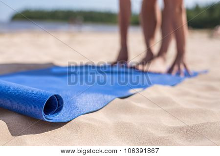 Girl doing yoga on a sunny day at the beach.