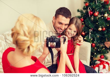 family, christmas, x-mas, winter, happiness and people concept - mother taking picture of smiling father and daughter