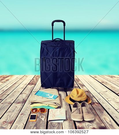 summer vacation, tourism and objects concept - travel bag, map, air ticket and clothes with personal stuff over wooden floor and sea background