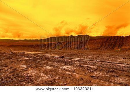 Abandoned mine - damaged landscape after ore mining, sunset sky