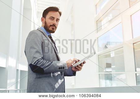 Young successful businessman using his touch pad while standing in modern office building inside