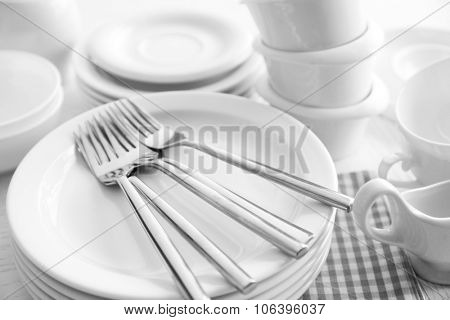 Set of white ceramics dishes on wooden table, closeup