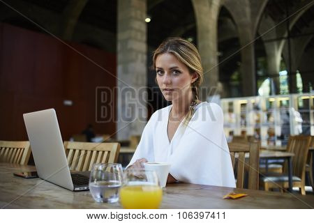 Attractive female freelancer working on portable laptop computer during recreation time