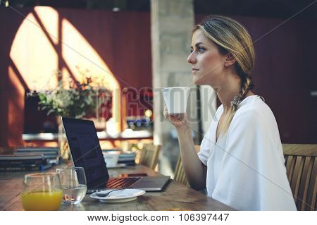 Beautiful dreamy female holding cup of coffee while sitting in front of open portable laptop compute