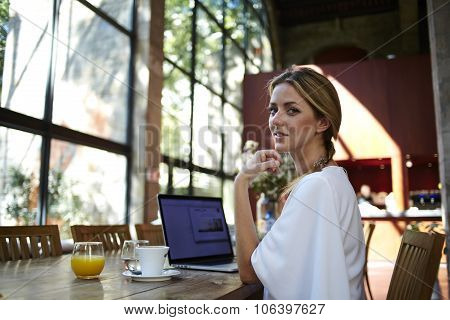 Charming female using portable laptop computer for distance job during recreation time