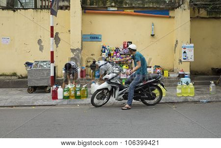 Vietnamese man on motorcycle buying cocking oil at a flea mobile stall