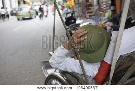 Tired Asian cyclo driver taking a nap on his rickshaw in Hanoi street.