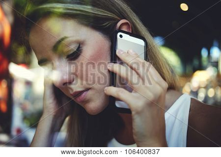 Beautiful woman having cell telephone conversation in coffee shop
