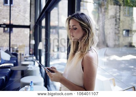 Charming smart woman read text on her digital tablet during recreation time