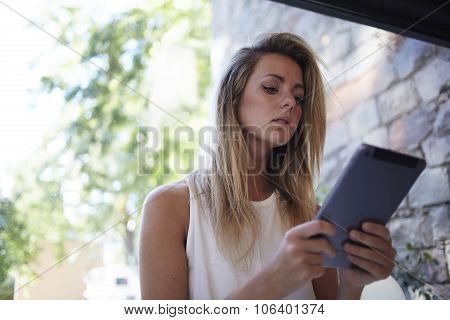 Young female student learning on-line via touch pad during free time
