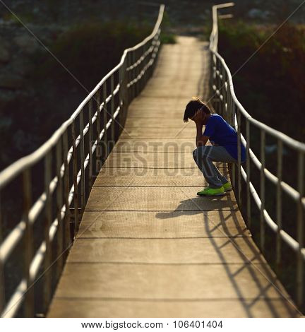 Lonely Boy Sitting On A Suspension Bridge