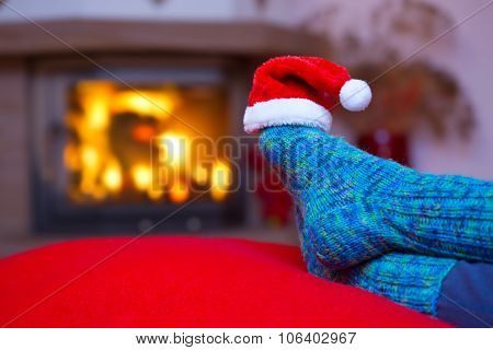 Feet in woollen blue socks and Santa hat .