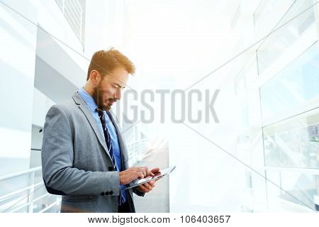 Young successful intelligent male in suit use digital tablet during work break