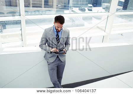 Confident man boss dressed in luxury clothes using digital tablet during work break