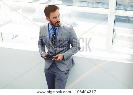 successful man entrepreneur dressed in elegant suit using digital tablet