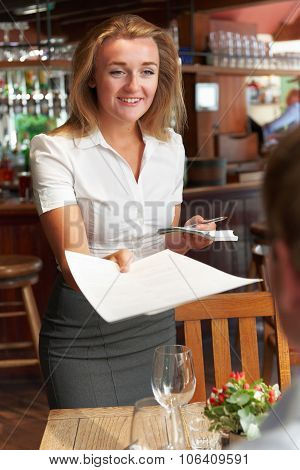 Waitress In Restaurant Handing Customer Menu