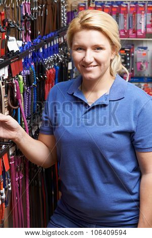 Sales Assistant In Pet Store With Display Of Dog Leashes