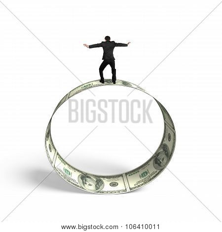 Man Balancing On Roll Of Dollar Bills