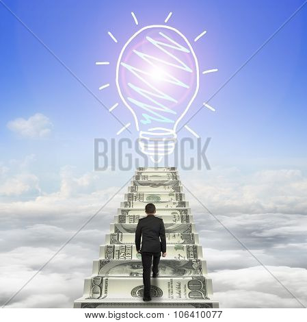 Businessman Climbing The Money Stairs Toward Light Bulb