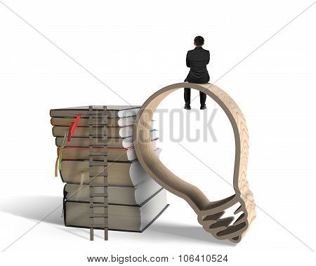 Businessman Sitting On Lightbulb Shape Wooden Frame With Books