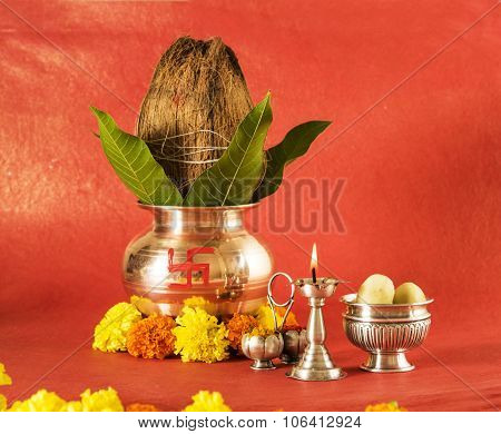 hindu puja elements, kalash with coconut and mango leaves,diya, haldi kumkum and indian sweet pedha