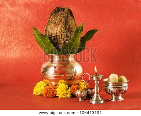 copper kalash with coconut and mango leaf with floral decoration, diya, haldi kumkum and sweet pedha