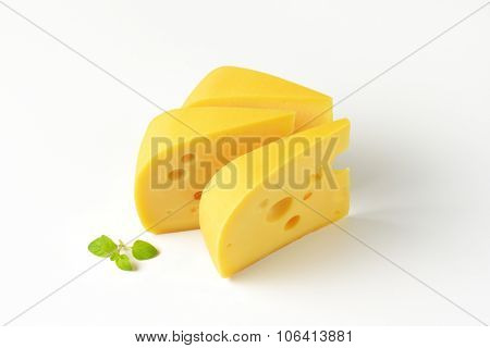 three wedges of fresh cheese on white background