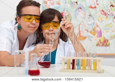 Young boy in elementary science class doing chemical experiment helped by teacher