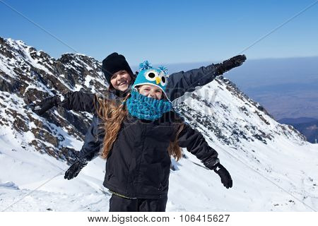 Happy kids on the top of mountain - enjoying the first snow
