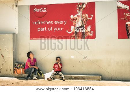Namibian Mother And Son Sitting On Floor Under A Coca Cola Billboard