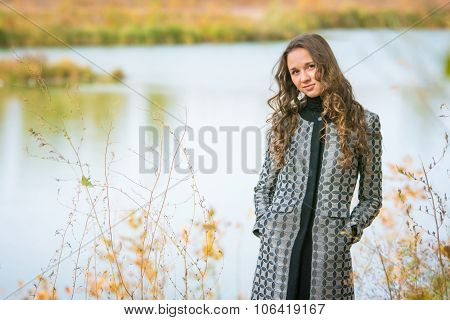 Portrait Of A Young Girl On The Background Of A Lake In Autumn Weather