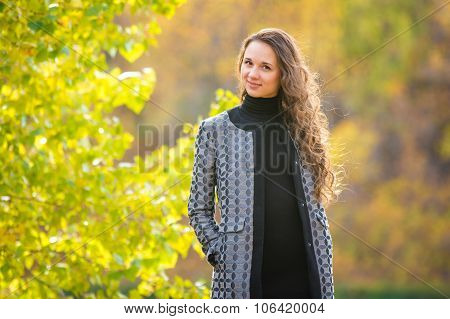 Cute Young Girl On The Background Of The Autumn Yellow Foliage