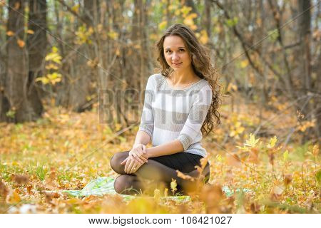 Young Beautiful Girl Sitting On A Rug On The Yellow Fallen Leaves