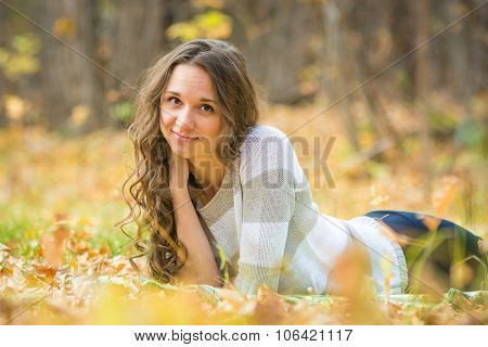 Young Beautiful Girl Lies On The Scourge In The Yellow Fallen Leaves