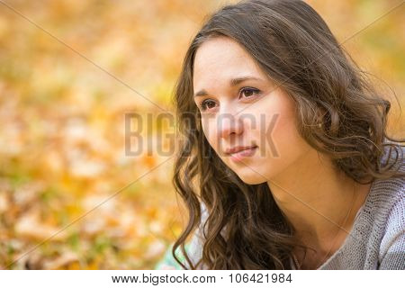 Close-up Portrait Of A Beautiful Young Girl On The Blurry Background Yellow Foliage