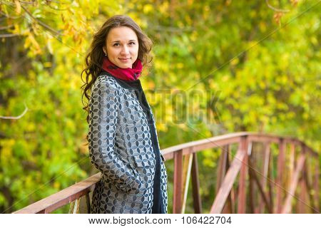 Half-length Portrait Of A Beautiful Young Girl Standing On The Bridge Against The Backdrop Of Autumn