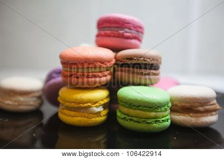 Four colorful macarons on black background