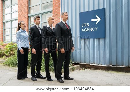 Businesspeople Waiting In A Row Near The Job Agency Signboard
