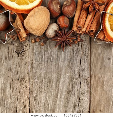 Border of baking ingredients and holiday spices over rustic wood