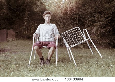 Lonely Teenage Boy With Two Chairs