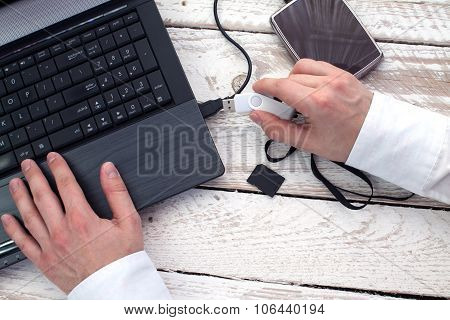 Man's hand puts pendrive into laptop.