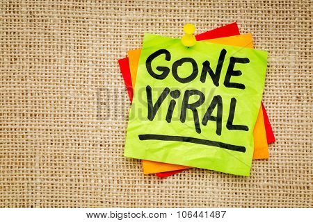 Gone viral - handwriting on a sticky note against burlap canvas