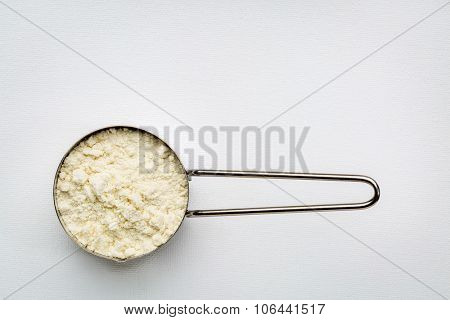 measuring metal scoop of whey protein powder against rustic white art canvas with a copy space