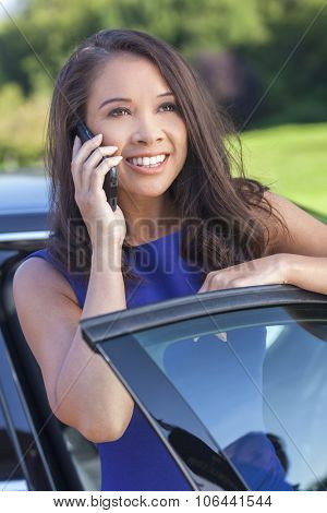 Portrait of a smiling happy young Asian Eurasian mixed race woman or businesswoman talking on her cell phone next to her car