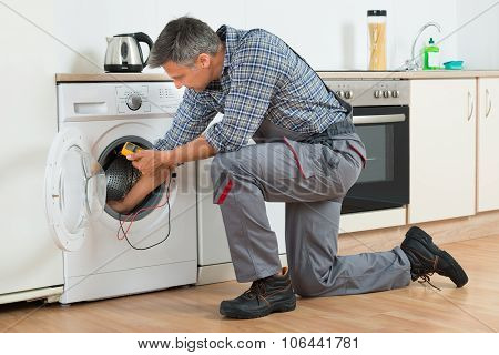 Repairman Checking Washing Machine With Digital Multimeter