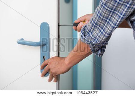 Technician Fixing Lock In Door With Screwdriver