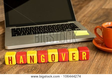 Hangover written on a wooden cube in front of a laptop