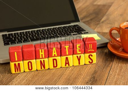 I Hate Mondays written on a wooden cube in front of a laptop
